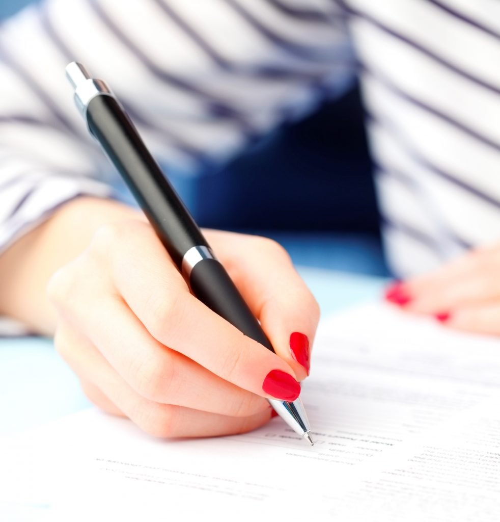 woman with red fingernails signing letter of withdrawal