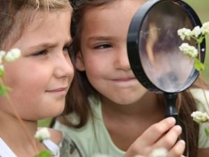 girls looking at flowers with magnifying glass while homeschooling in springtime