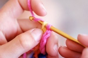 5 Things Kids Can Learn from Crochet, kid using crochet needle and yarn