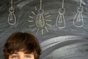 Deschooling -- teen in front of blackboard w/drawn lightbulbs above his head