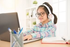 Favorite Free Homeschool Curriculum, girl at computer with headphones