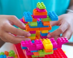child building with lego blocks