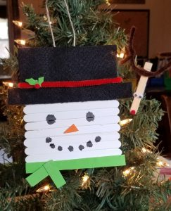 snowman popsicle stick ornament hanging on christmas tree