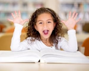 excited little girl reading book